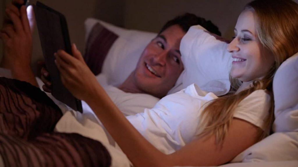 casal seguro com tablets na cama