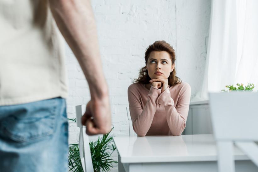 Mulher sentada a mesa observa as ameaças do marido