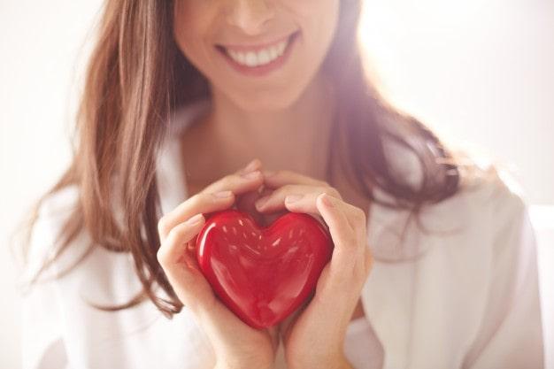 Mulher segurando um coração vermelho nas mãos. auto conhecimento e amor próprio